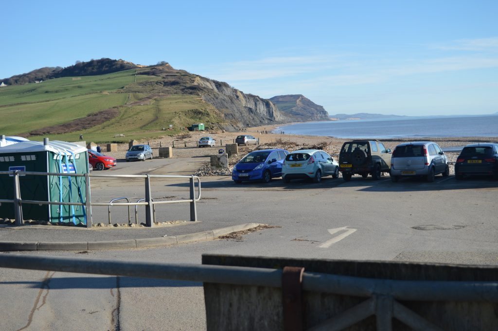 First view of Golden Cap in the distance.  Tide is in.   SOFT ROCK CAFÉ  Refreshments and takeaway food - the green building on the beach in the distance