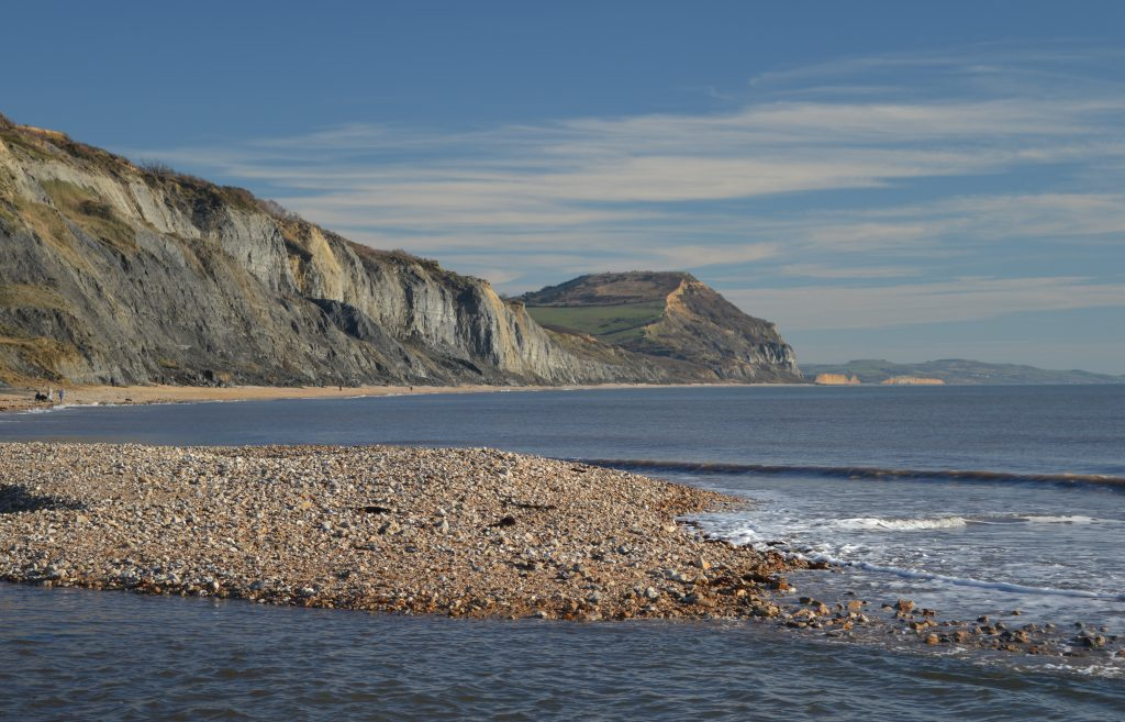 On the beach looking East towards Golden Cap.  The tide in. The Jurassic Coast